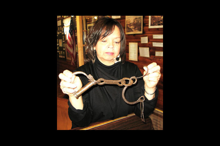 Curator Shannon Prince holds up shackles used on slaves.
