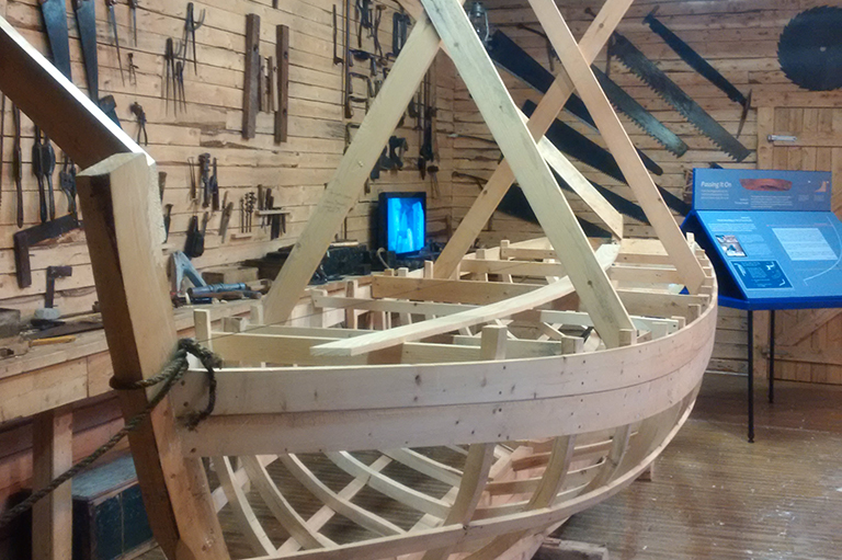 This image shows the wooden frame of a boat in a building.