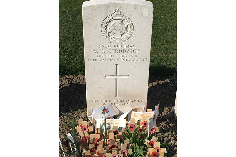 Image of a head stone with handmade crosses and poppy in front.