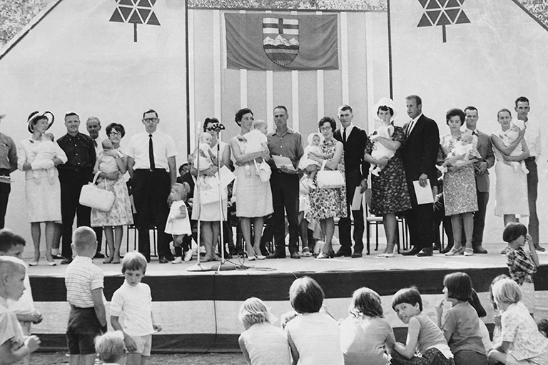 This image shows parents and their children standing on a stage.