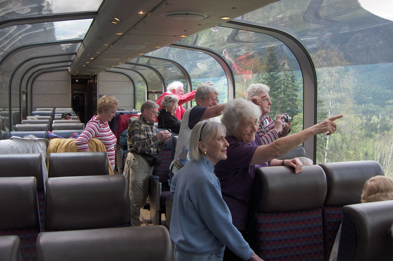 Train passengers looking out from domed observation lounge.