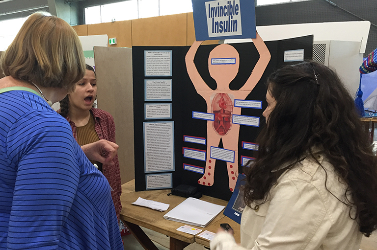 "This image shows two students speaking with a judge in front of their project called ""Invincible Insulin."""