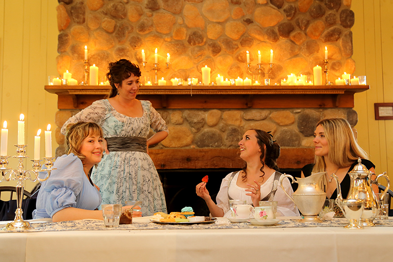 Women sit and stand at the head table with lit candles behind them.