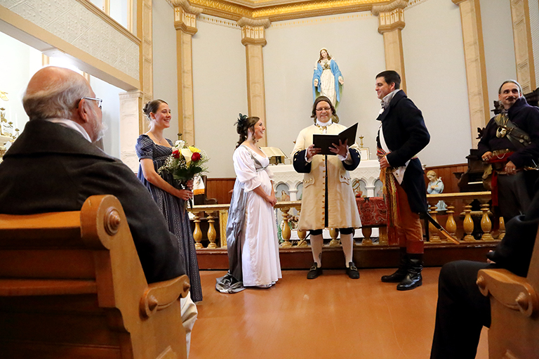 A wedding couple exchange vows in a historic chapel.