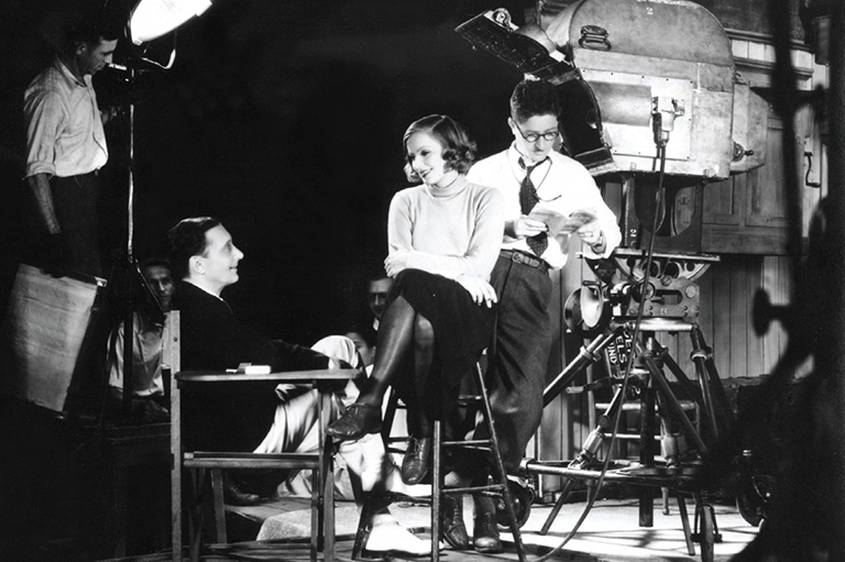large camera and a man and woman face each other on a film set.
