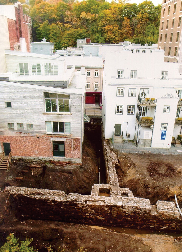 An aerial photo of white building with an archaeological site directly in front of them.