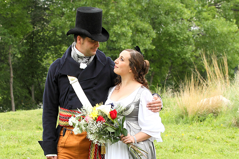 A wedding couple in historic costume stand in a field.