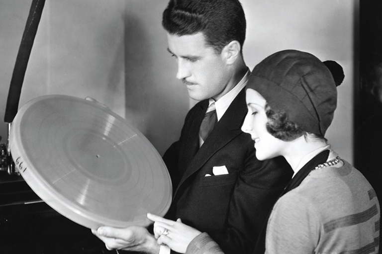 A man and a woman holding a disk, both are looking to the left at the disk.