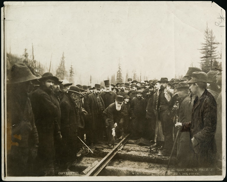This is the iconic last spike photo of a group of men standing around Donald A Smith driving a spike into the railway.