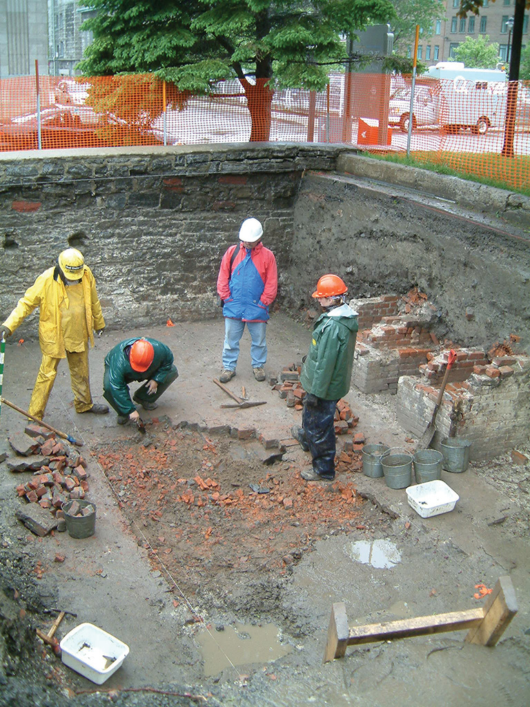 People wearing hard hats standing in an archaeological site looking at the ground