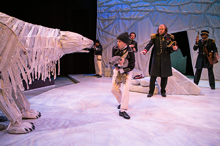 Image shows three people on stage walking fearfully around a large polar bear. The polar bear is made of art supplies.