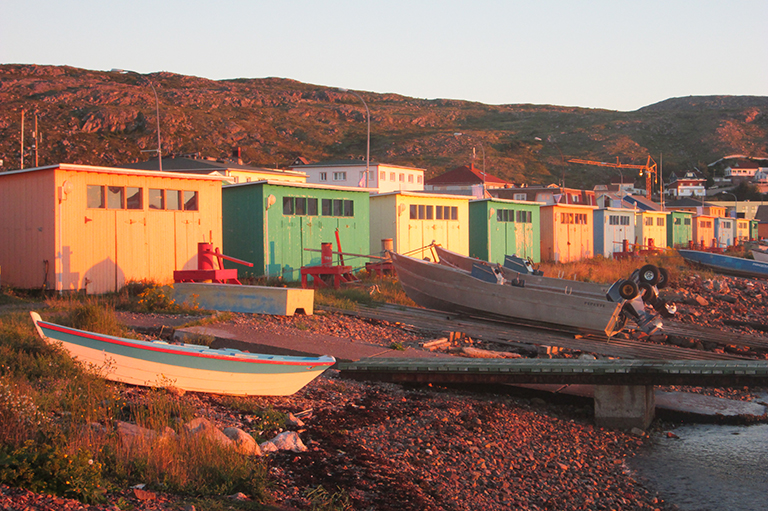 This image shows different coloured (orange, green, yellow) boathouses glowing in a morning sunrise.