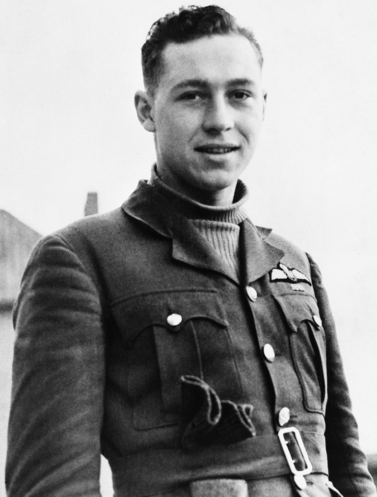 This image shows a young man looking into the camera with a half smile. He is wearing a turtleneck and a blazer.