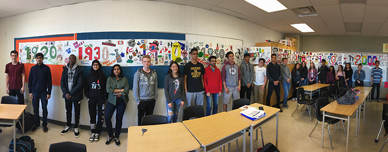 This image shows students standing in front of their timeline of Canada.