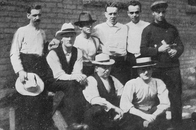 A group of eight men pose for a photo.