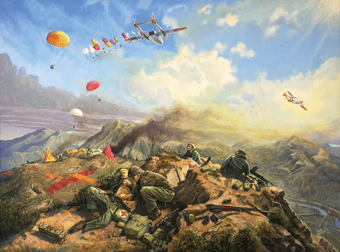 Men crouched on a ridge, a plane flying overhead with people and parachutes jumping out.