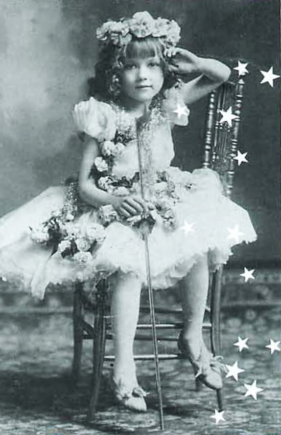 a young girl with bangs, a flower crown, and a white dress sitting in a chair.