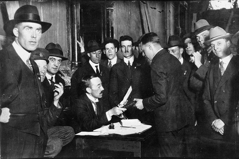 A group of men in black suits standing around a man sitting at a table with papers and a pen.