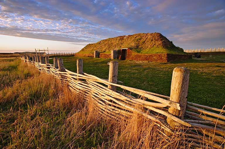 This image shows a wooden fence close to the camera and in the distance a Norse building on a blue and cloudy sky.