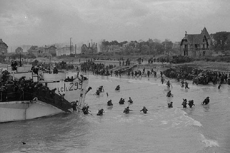 This image shows uniformed soldiers walking from a ship onto a beach through the water.
