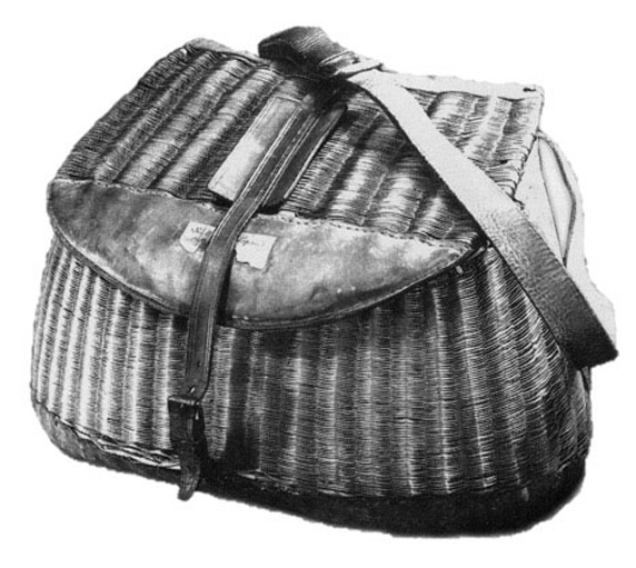 A grey scale image of a basket with a shoulder strap.