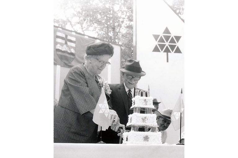This image shows a man and a women cutting a cake.
