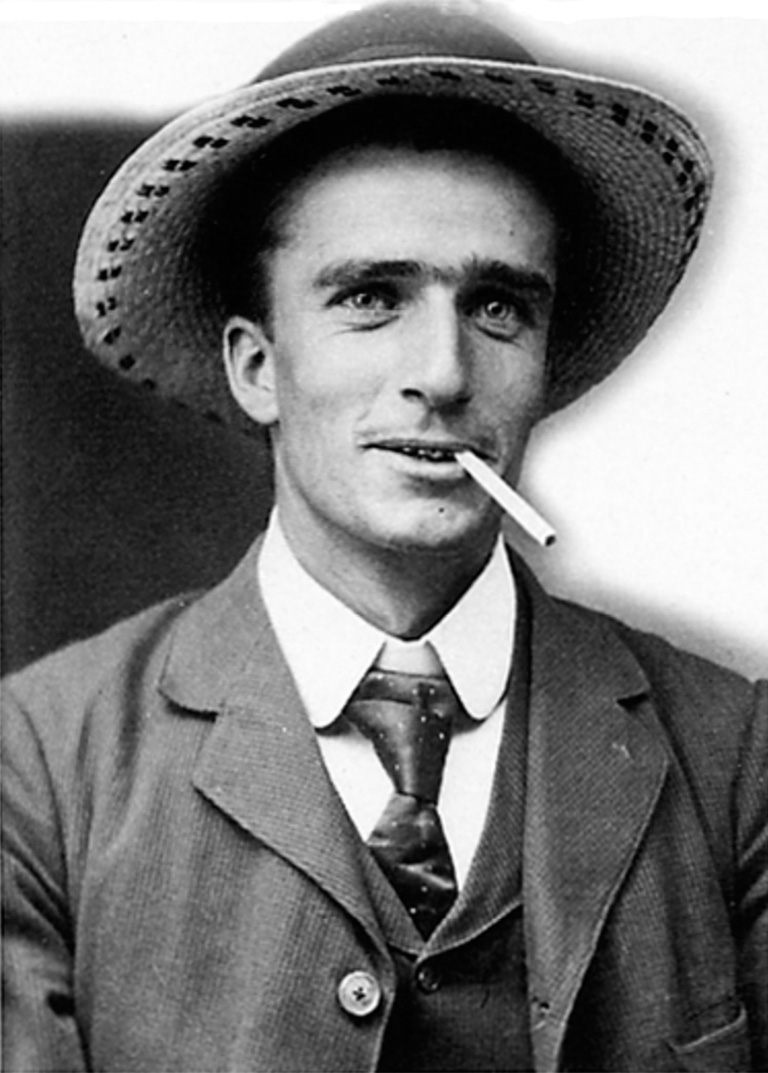 Man wearing a suit and a hat smoking a cigarette