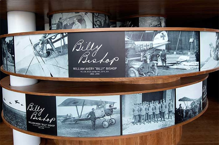 Exhibit display showing historical black-and-white photographs of airplanes.