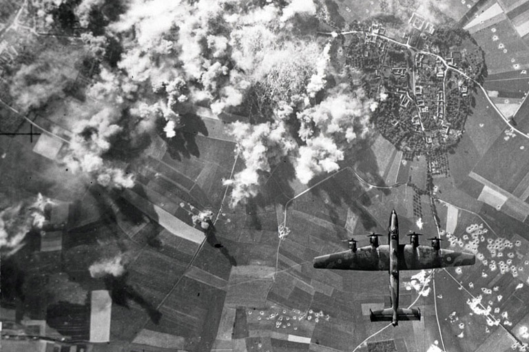 Plumes of smoke rise over a German city as a Halifax bomber completes its bombing run.