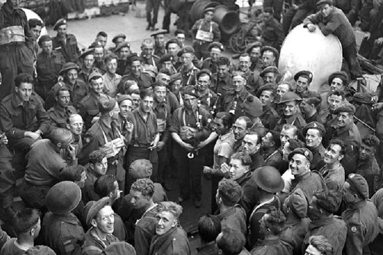 This image shows a man playing the bagpipes and many other men gathered around him.