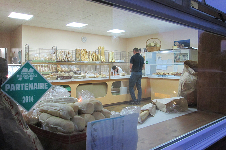 This image shows a photo of the inside of a bakery filled with bread and one customer in the store.