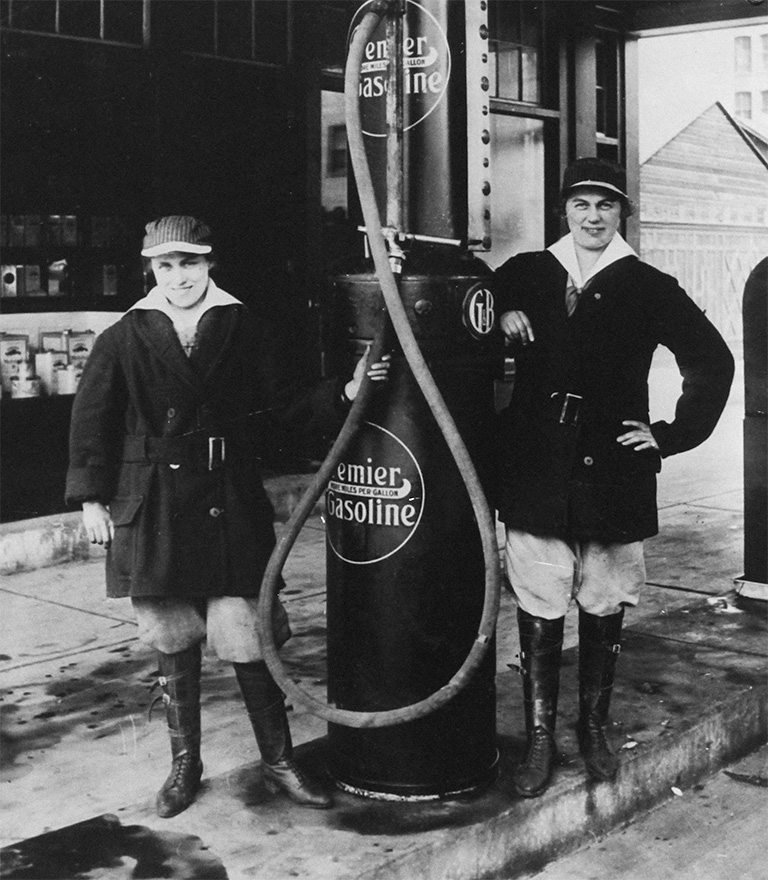 Two women stand beside a gas pump.