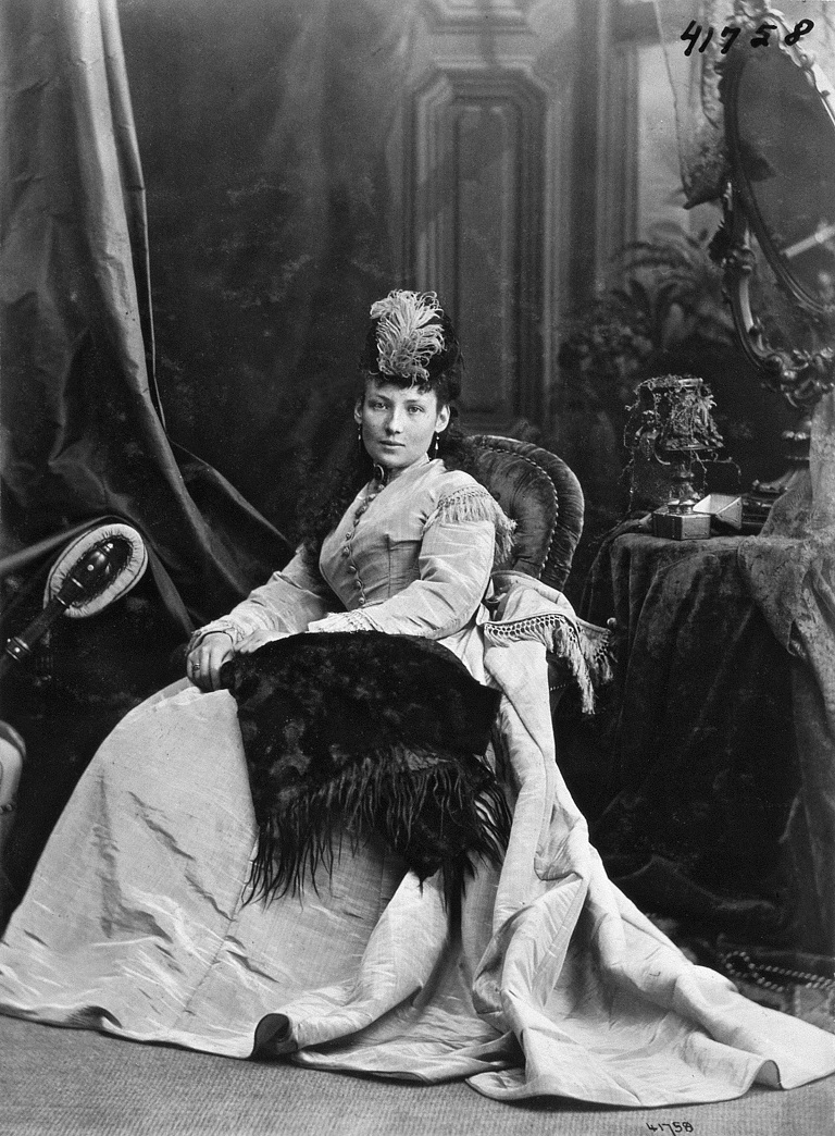 This is a black and white portrait photograph of a women named Miss McArthur. She is seated on a chair in front of a detailed background.