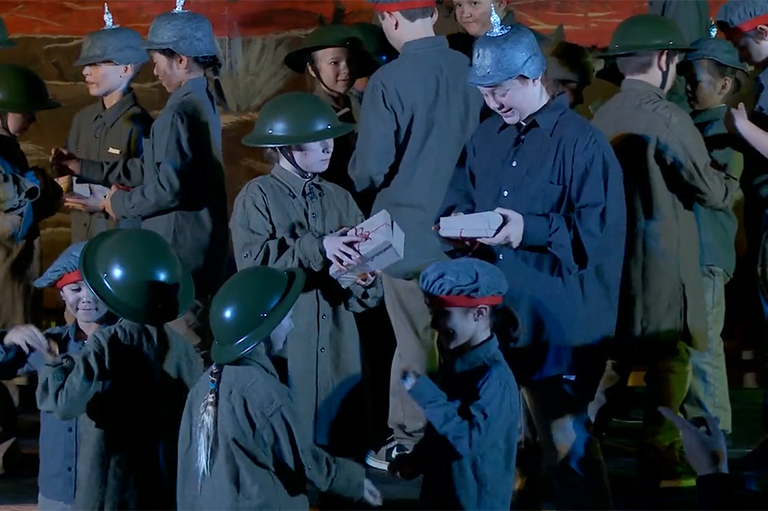 This image shows student performing the exchange of gifts between the German and Allied forces during the Christmas Truce of the First World War.