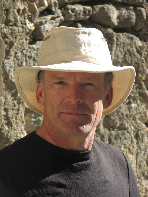 Headshot of Ian Roberts wearing a white hat, black tshirt, in front of a rock wall.