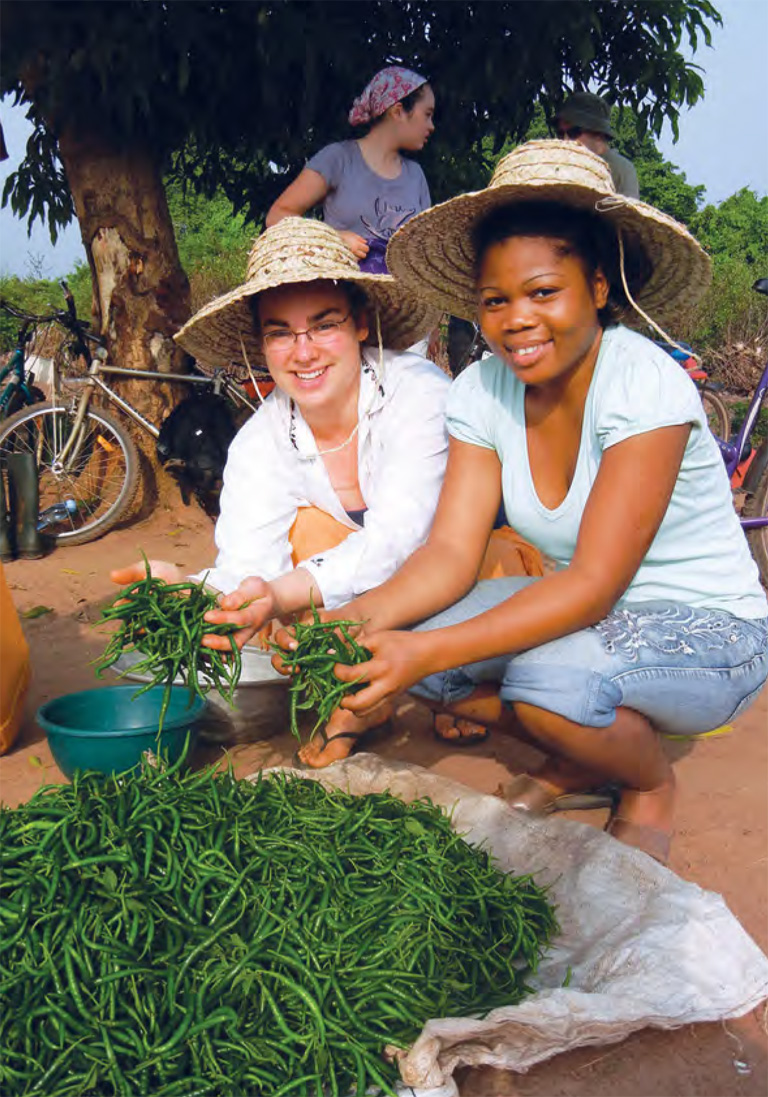 Colour photo of two young women tending a garden.