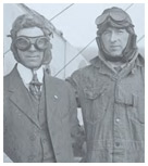 Black and white photo of twom men in aviation gear standing against a bi-plane.
