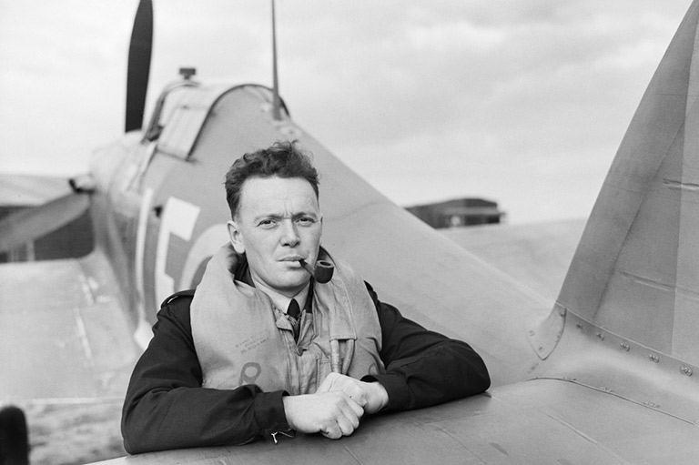This image shows a man leaning forward on an airplane wing with a tobacco pipe in his mouth.