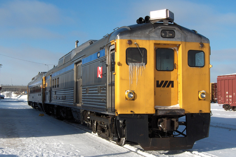 Colour photograph of train with snow on the ground.