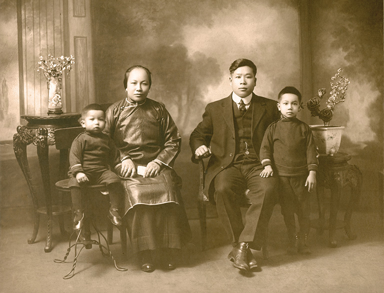 Two adults sitting in chairs, and a child on each side.