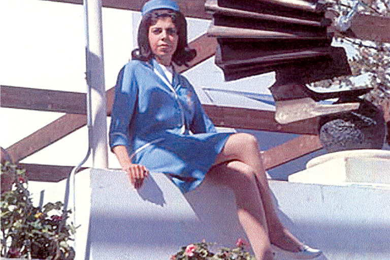 Woman in modern blue uniform sitting cross-legged.