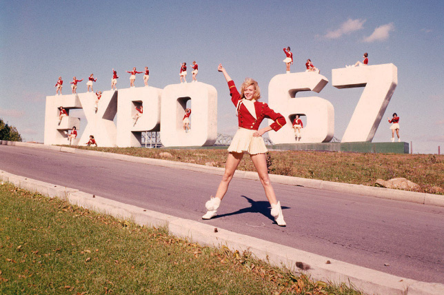 Majorettes standing on large Expo 67 sign.