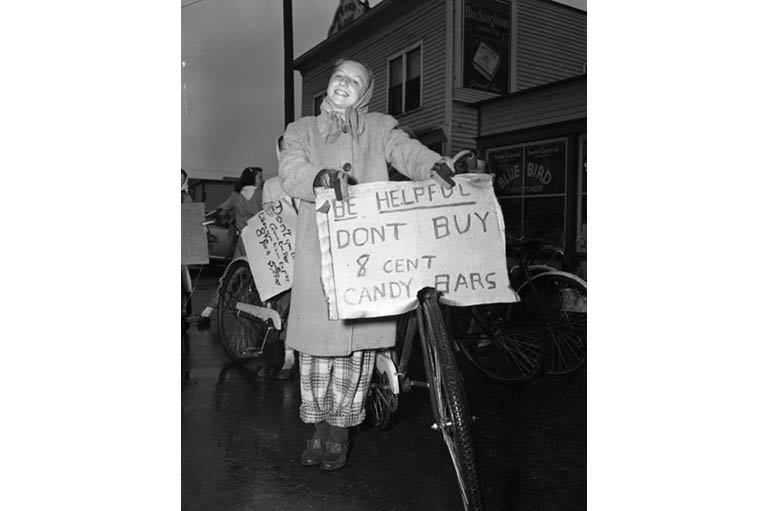 Girl with bike shows off her protest sign on handle bars.