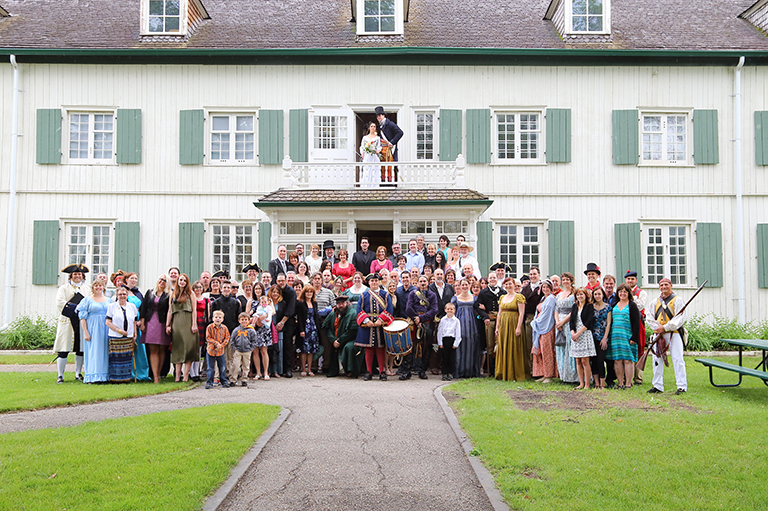 Wedding guests and couple pose for a photo in front of Musée de Saint-Boniface.