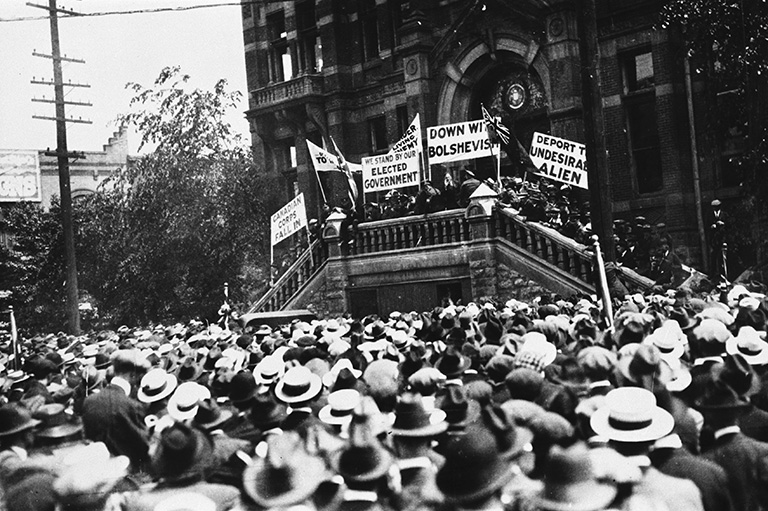 A crowd of people facing away from the camera and looking at people holding signs standing on the stairs in front of a building.