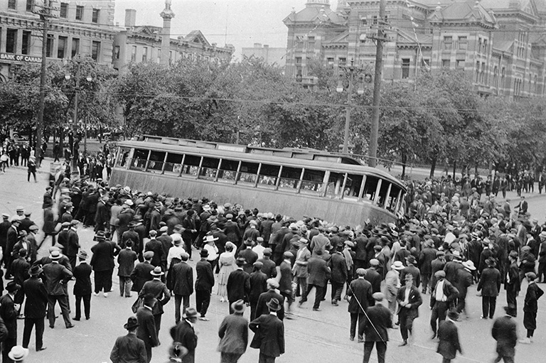 A crowd of people pushing over a streetcar.