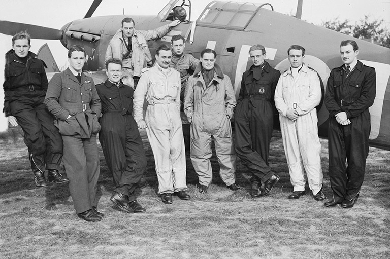 This image shows a group of men in uniforms leaning against an airplane