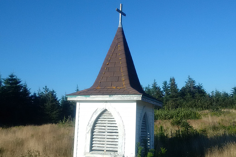 This image shows the steeple of a church in a cemetery.