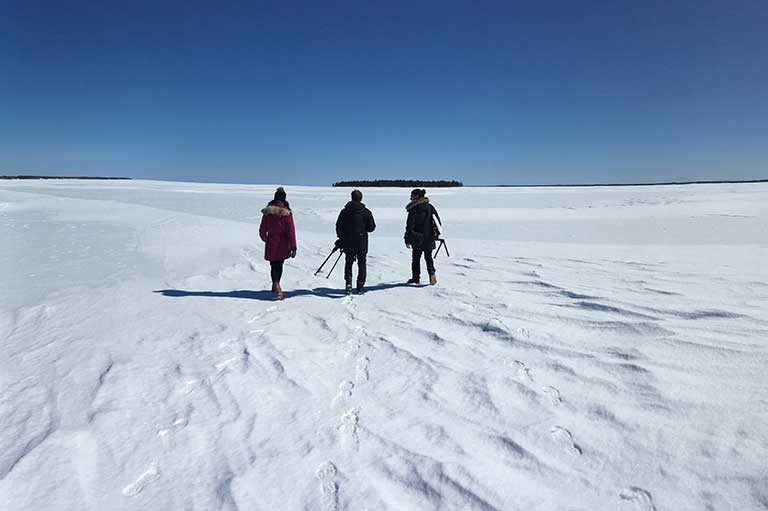 Snow landscape and bright blue sky with three people standing side by side facing away from the camera.