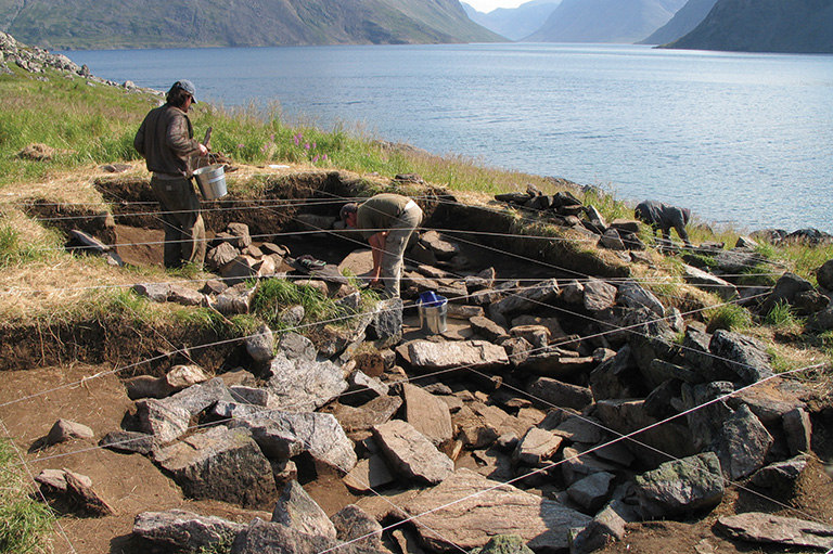 An coastal archaeological site with rocks and ropes and people working.